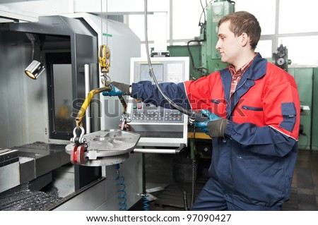 manufacture worker moving detail by beam crane into modern cnc machine tool for metal cutting processing at factory workshop