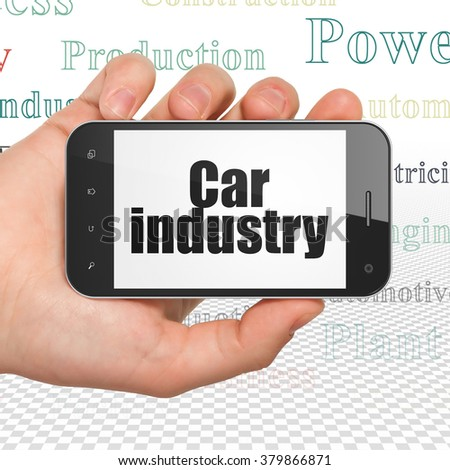 Manufacuring concept: Hand Holding Smartphone with Car Industry on display - stock photo