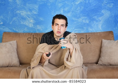 Manwith soda can and remote control stares ahead - stock photo