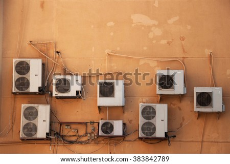 many air condition machines on a brown wall - stock photo
