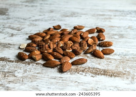 Many almonds over a wooden table, background  - stock photo