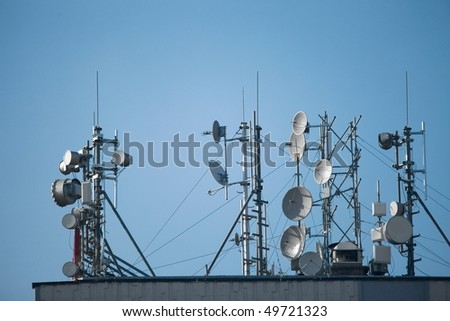 Many antennas on the roof of a tall building - stock photo