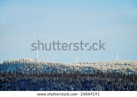 Many antennas on top af a mountain  in the forest on winter - stock photo