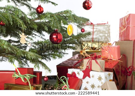 many are wrapped Christmas presents under a Christmas tree with cookies and nuts