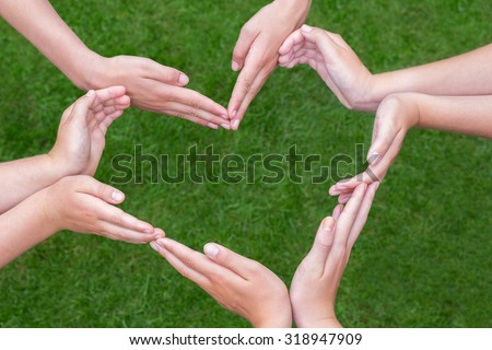 Many arms and hands of girls make heart shape above green grass - stock photo