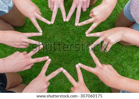 Many arms of girls with hands making ten pointed star above green grass - stock photo