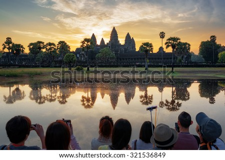 Many Asian tourists taking picture of ancient temple Angkor Wat at sunrise. Siem Reap, Cambodia. Towers of Angkor Wat reflected in lake at dawn. Angkor Wat is a popular tourist attraction. - stock photo
