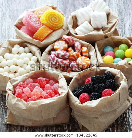 Many assorted sweet sugar candies on vintage wooden background - stock photo