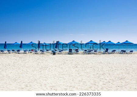 Many beach chairs and umbrellas on white sand sea beach with a blue sky. Concept for rest, relaxation, holidays, spa, resort.  - stock photo
