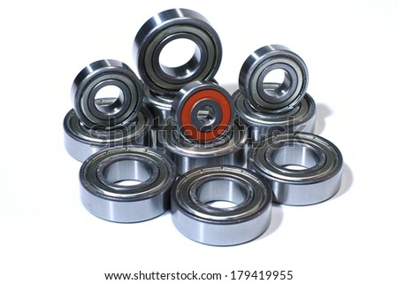 Many bearings of different sizes together. White background.