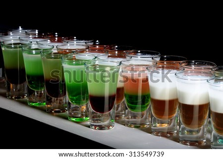 Many beautiful colorful alcoholic tasty hard shot cocktails in drinking glasses green brown red and white colors standing in row on black studio background, horizontal picture - stock photo