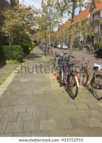 Many bikes parked on a residential street in the Netherlands - stock photo