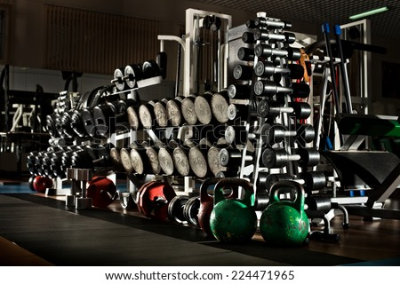 many black dumbbells in gym room, horizontal photo - stock photo