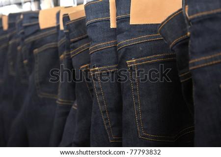 Many blue denim jeans on coat hanger. - stock photo