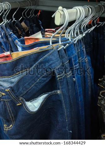 many blue jeans hanging on a rail - stock photo