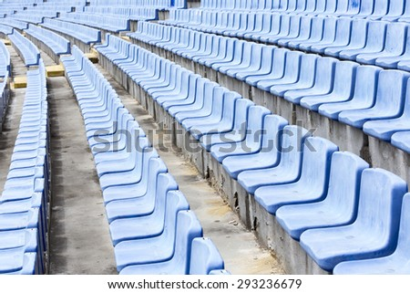 Many blue old seats at a stadium which need replacement.