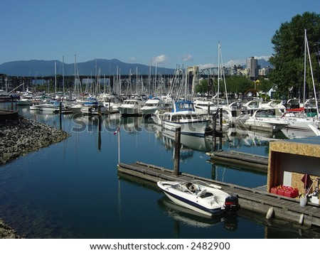 Many boats in a marina with Vancouver Canada in the background. - stock photo
