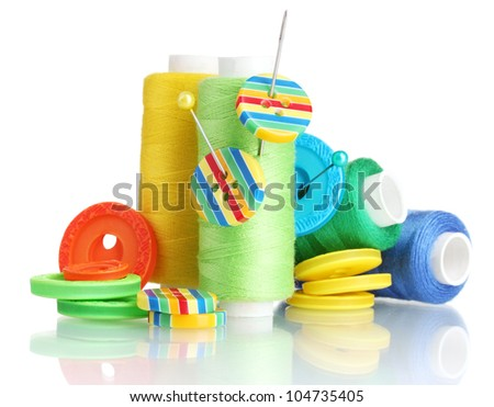 Many bobbin of thread with needle and buttons isolated on white - stock photo