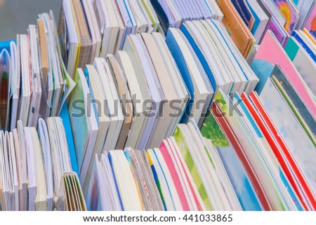 Many books pile on wooden table at library.