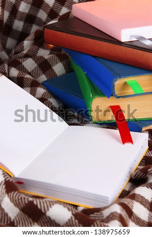 Many books with bookmarks on plaid - stock photo