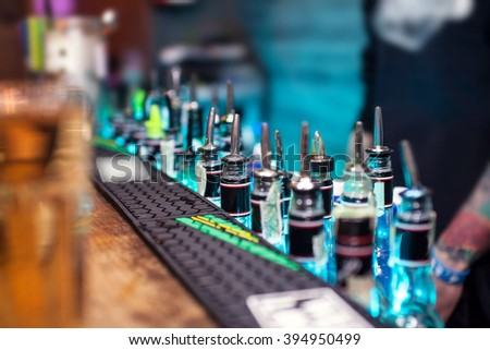 Many bottles with alcoholic beverages on the bar counter. - stock photo