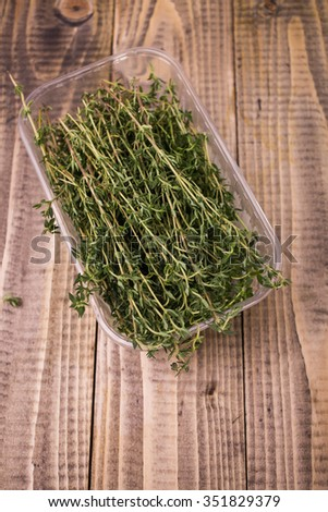 Many branches of aromatic fresh green colored herb rosemary ingredient for piquant taste of dish in plastic food container on wooden background top view closeup, horizontal picture - stock photo