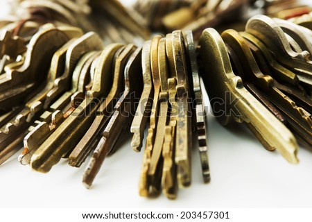 Many brass and chrome old keys on white table. Security and encryption, concept image. - stock photo