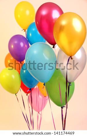 Many bright balloons on orange background - stock photo