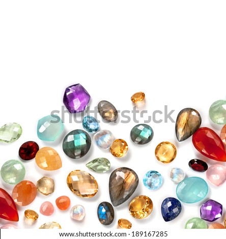 Many bright gems on the white background. Mix of real stones: labradorite, garnet, citrine, amethyst, blue topaz, peach and rainbow moonstone, rose quartz, lapis lazuli, carnellian ... - stock photo
