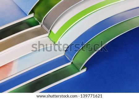 Many bright open magazines close-up - stock photo