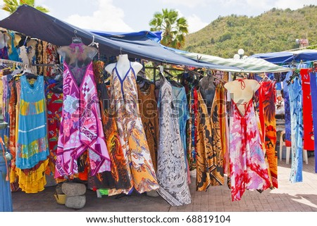 Many brightly colored and dyed dresses hanging in a tropical market
