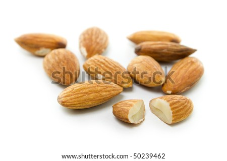 Many brown almonds isolated on white