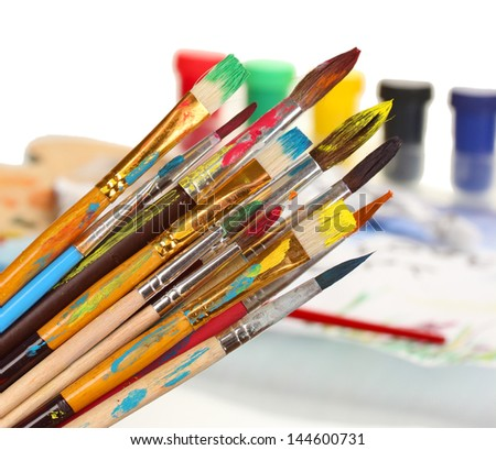 Many brush in paint on bright background - stock photo