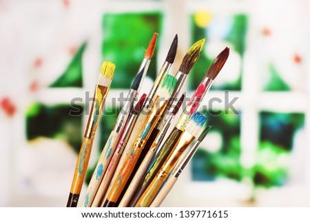 Many brush in paint on window background - stock photo
