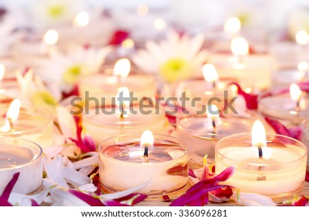 many burning candles with purple flower petals  - stock photo