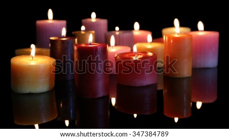 Many burning small candles on dark background