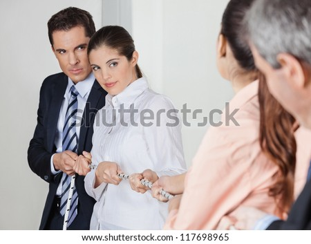 Many business people pulling on a string in the office - stock photo