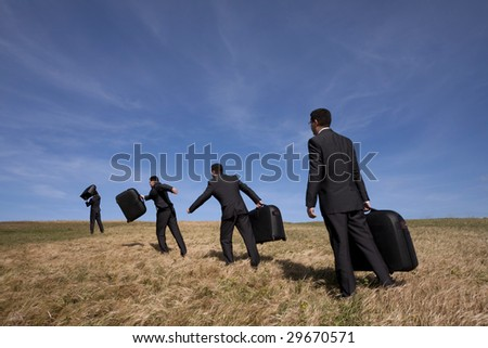 many businessmans in the field walking with his luggage - stock photo