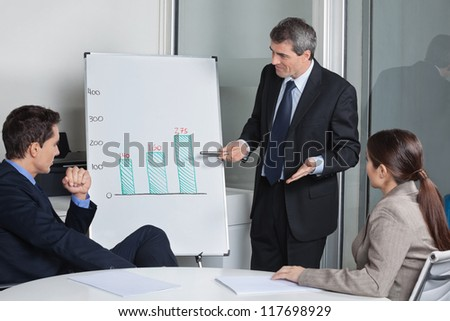 Many businesspeople listening to presentation with a whiteboard in a meeting - stock photo