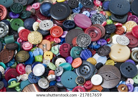 Many buttons of various shapes and colors. Bright background for needlework.