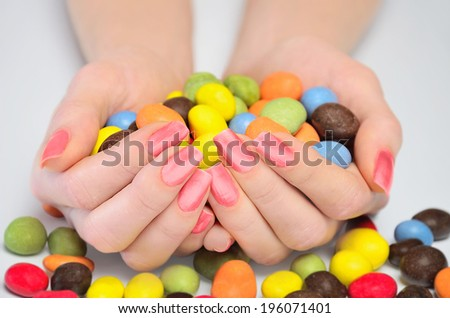 Many candies in woman hand - stock photo