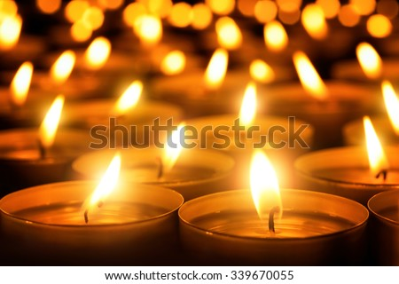 Many candle flames glowing in the dark, create a spiritual atmosphere - stock photo