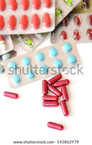 many capsules and pills on white background