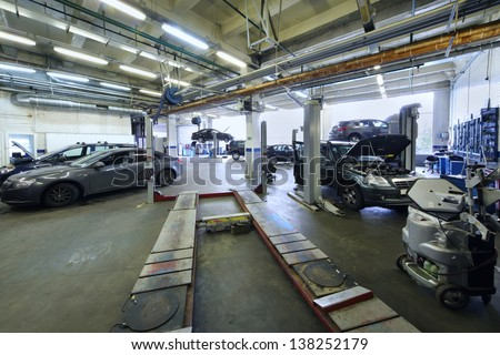 Many cars stand in car garage with special equipment for repair. - stock photo