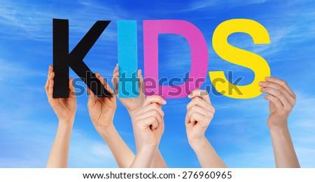 Many Caucasian People And Hands Holding Colorful Straight Letters Or Characters Building The English Word Kids On Blue Sky - stock photo