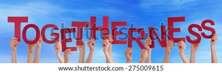 Many Caucasian People And Hands Holding Red Letters Or Characters Building The English Word Togetherness On Blue Sky - stock photo