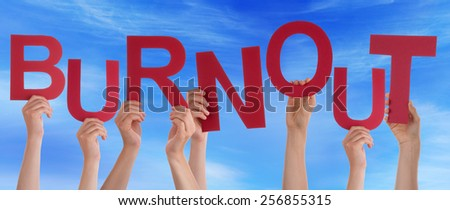 Many Caucasian People And Hands Holding Red Letters Or Characters Building The English Word Burnout On Blue Sky - stock photo