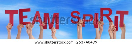 Many Caucasian People And Hands Holding Red Letters Or Characters Building The English Word Team Spirit On Blue Sky - stock photo