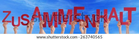 Many Caucasian People And Hands Holding Red Letters Or Characters Building The German Word Zusammenhalt Which Means Solidarity On Blue Sky - stock photo