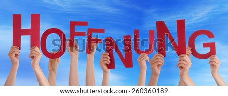 Many Caucasian People And Hands Holding Red Straight Letters Or Characters Building The German Word Hoffnung Which Means Hope On Blue Sky - stock photo